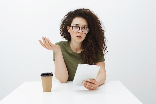 Mulher encantadora confusa sem noção com cabelo encaracolado nos óculos, levantando a mão em um gesto questionador, sentada à mesa