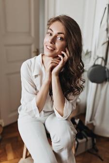 Mulher encantadora de camisa branca posando em uma sala iluminada