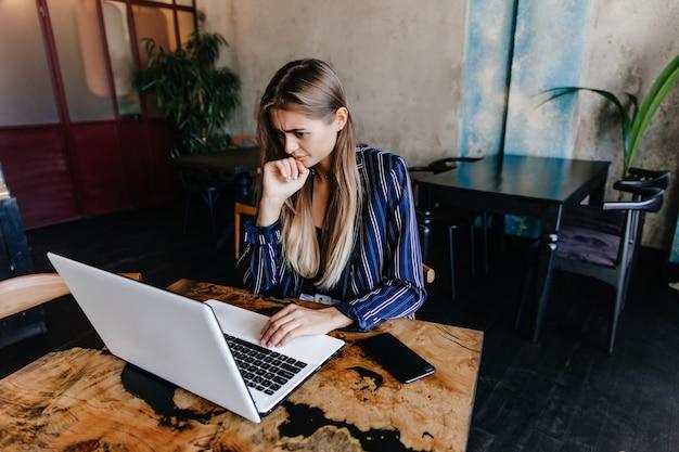 Mulher encantadora de casaco azul, olhando para a tela do computador. foto interna da estudante de cabelos compridos, estudando no café.