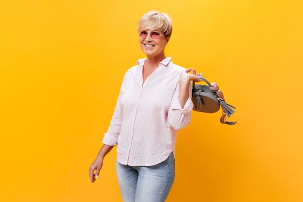 Mulher encantadora de óculos escuros e camisa rosa posando com bolsa em fundo laranja