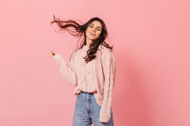 Mulher encantadora de suéter rosa brinca com cabelo em fundo isolado. senhora de jeans ri e olha para a câmera.