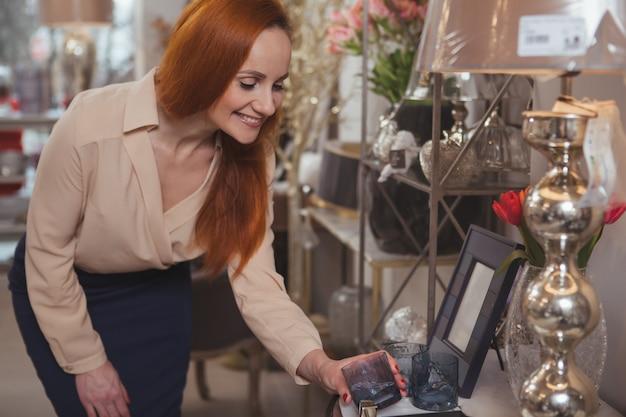 Mulher encantadora, desfrutando de compras na loja de decoração para casa