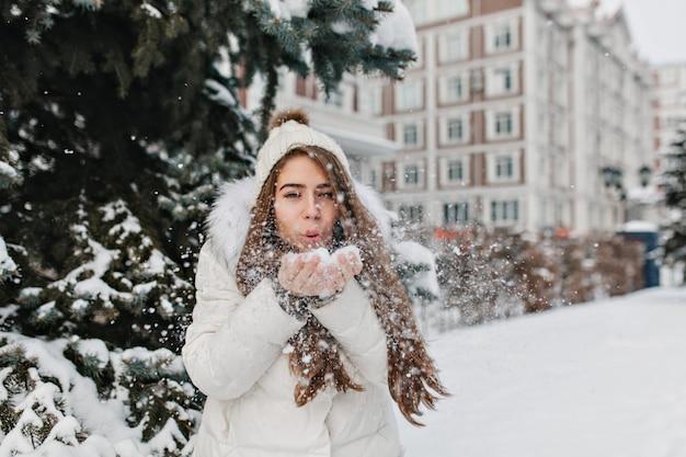 Mulher encantadora e alegre soprando flocos de neve das mãos em dia de inverno ao ar livre na rua.