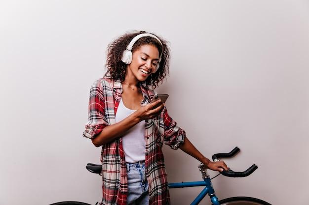 Mulher encantadora e elegante em fones de ouvido, lendo mensagem de telefone. garota africana bem vestida com bicicleta segurando o smartphone.