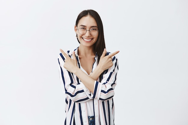 Mulher encantadora e feliz de óculos e blusa listrada, cruzando as mãos sobre o peito e apontando para a esquerda e a direita enquanto sorri alegremente, posando sobre uma parede cinza