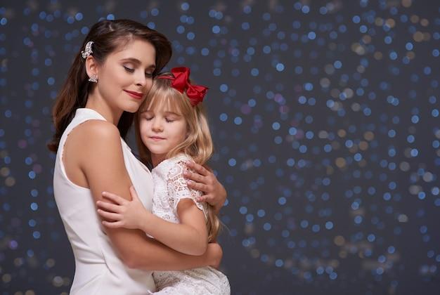 Mulher encantadora e filha apaixonada se abraçam