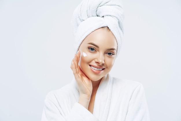 Mulher encantadora e relaxada aplica creme no rosto, se preocupa com a pele, toca a bochecha com a mão, sorri delicadamente vestida com roupão de banho, toalha enrolada no cabelo lavado, isolado no branco