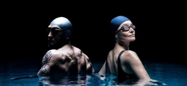 Mulher encantadora e um homem forte posando na piscina