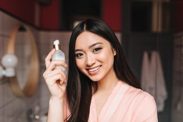 Mulher encantadora em roupão de seda clara segurando um frasco de soro facial e sorrindo