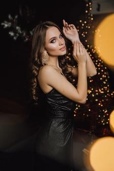 Mulher encantadora em um cenário noturno posando em uma árvore de natal