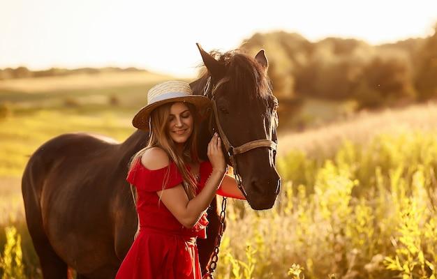 Mulher encantadora em um chapéu de feno e vestido vermelho fica com um cavalo no campo verde