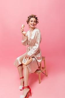 Mulher encantadora em um manto rosa sorri, se senta na cadeira e segura o telefone na parede isolada