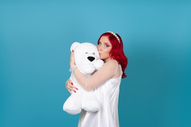 Mulher encantadora em um vestido branco com cabelo ruivo no perfil beija a bochecha de um ursinho de pelúcia branco
