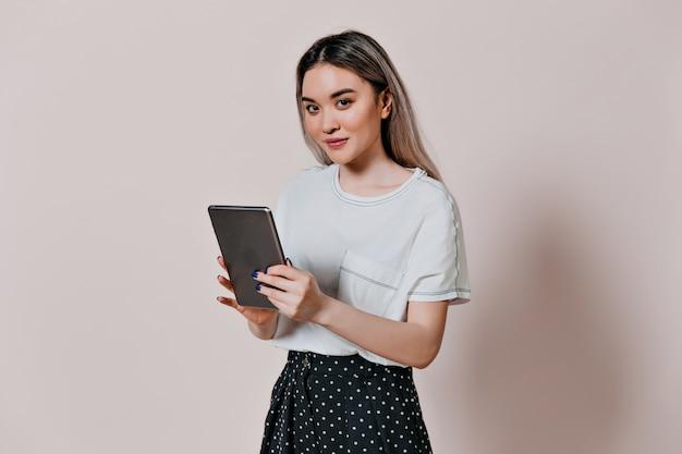 Mulher encantadora em uma camiseta branca segurando um tablet no computador