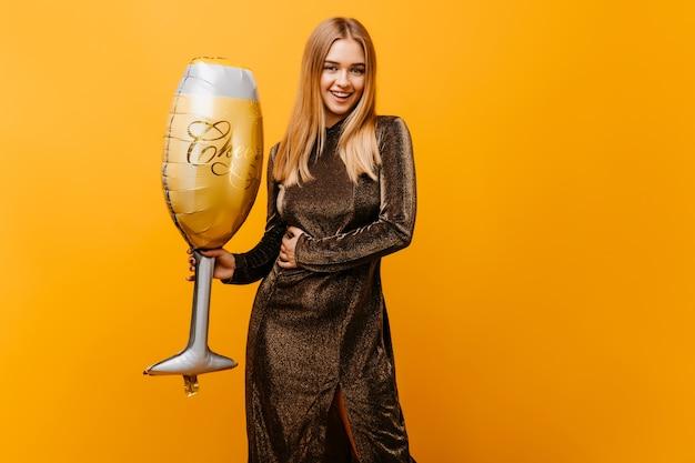 Mulher encantadora em vestido brilhante de ling, comemorando o aniversário. retrato de uma mulher bonita sorridente em pé na laranja com um grande copo de vinho.
