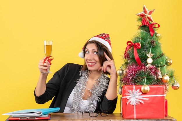 Mulher encantadora emocional de terno com chapéu de papai noel e decorações de ano novo, criando vinho no escritório em amarelo isolado
