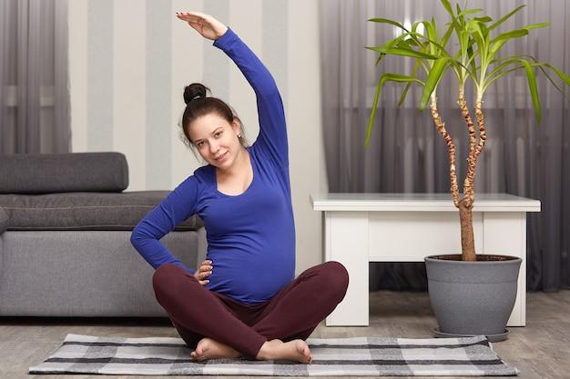 Mulher encantadora espera filho, pratica esporte em casa, cuida de sua saúde, usa suéter azul e perneiras, tem cacho na cabeça, levanta uma mão, tem estilo de vida saudável durante a gravidez.