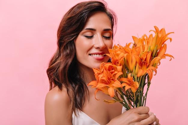 Mulher encantadora inala agradável perfume de flores e sorri