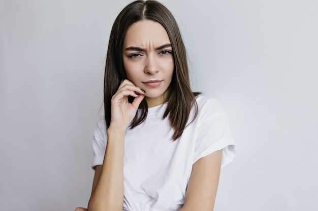 Mulher encantadora infeliz em posar de t-shirt. garota européia de cabelos escuros desagradável em frente a uma parede branca.