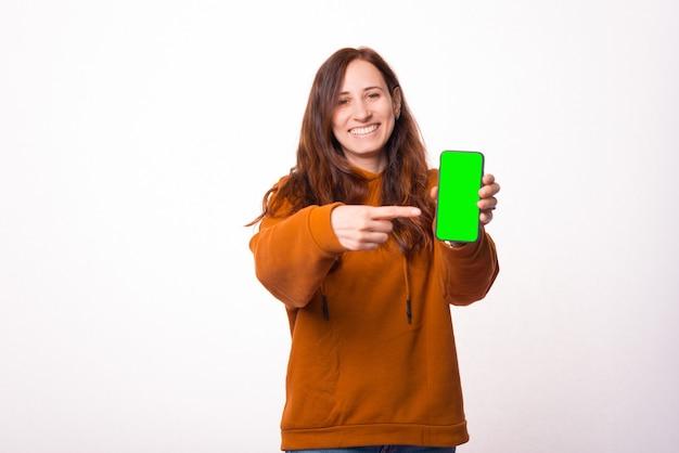 Mulher encantadora jovem hippie apontando para a tela verde no smartphone.