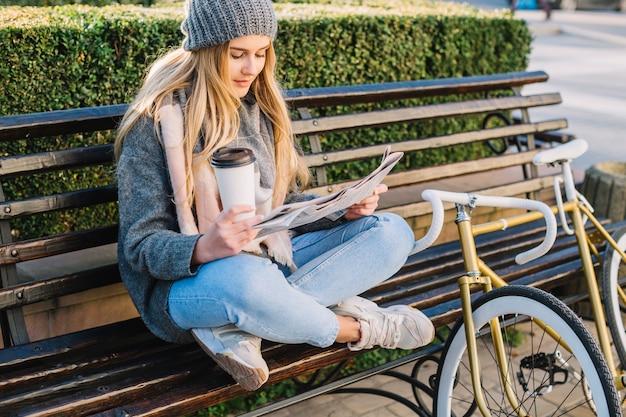 Mulher encantadora lendo jornal no banco