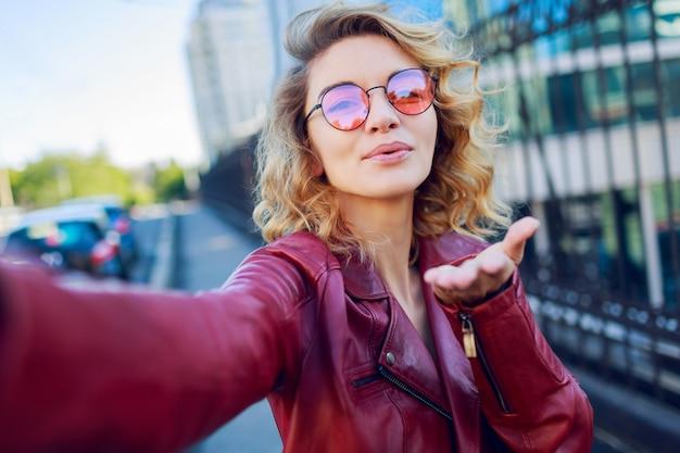 Mulher encantadora manda beijo no ar e faz auto-retrato. penteado loiro encaracolado. óculos cor de rosa e jaqueta de couro na moda outono.