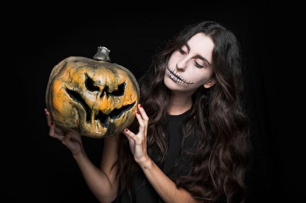 Mulher encantadora mostrando a abóbora de halloween
