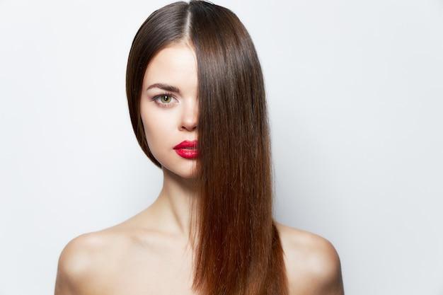 Mulher encantadora, ombros nus, lábios vermelhos, cabelo cobrindo o rosto, pele cuidados