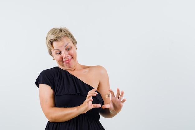 Mulher encantadora posando como se estivesse segurando algo em uma blusa preta