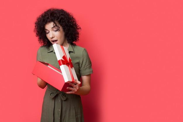 Mulher encantadora se perguntando ao abrir a caixa de presente em uma parede vermelha do estúdio