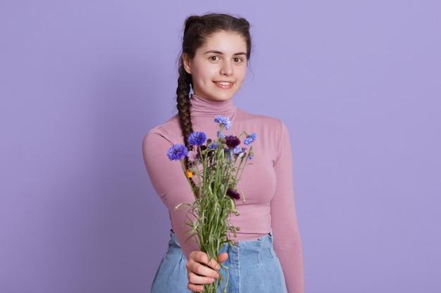 Mulher encantadora segurando buquê de flores do campo, feminino oferece flores para alguém, garota com tranças posando isolado sobre uma parede lilás, adolescente sorridente.