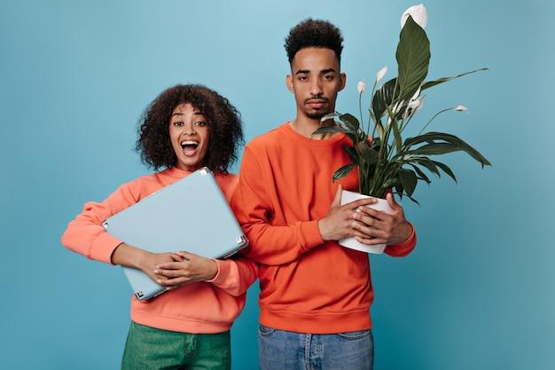 Mulher encantadora segurando uma mala azul e o namorado segurando uma planta