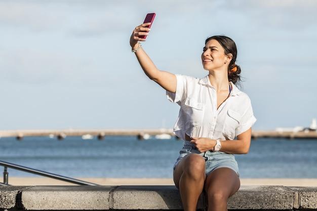 Mulher encantadora tirando selfie em smartphone no aterro