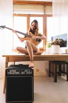 Mulher encantadora tocando violão na mesa