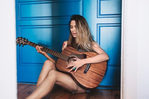 Mulher encantadora tocando violão perto da parede azul