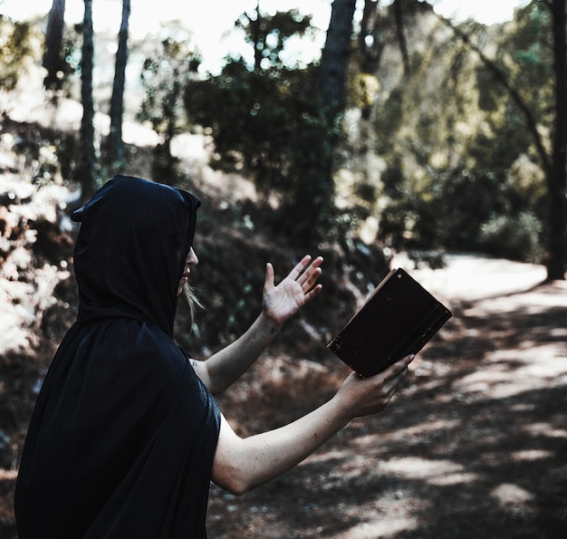 Mulher encapuzada com livro conjurando na floresta iluminada pelo sol