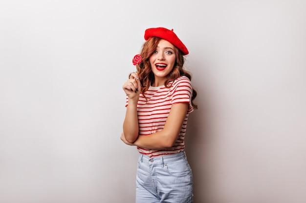 Mulher encaracolada alegre comendo pirulito na parede branca. encantadora garota francesa na boina posando com doces.