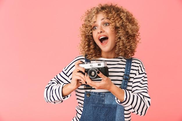 Mulher encaracolada animada dos 20 anos fotografando em uma câmera retro em pé