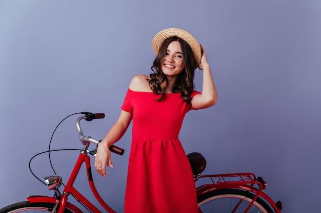 Mulher encaracolada bem humorada com chapéu de verão, expressando emoções positivas enquanto olha para a câmera.