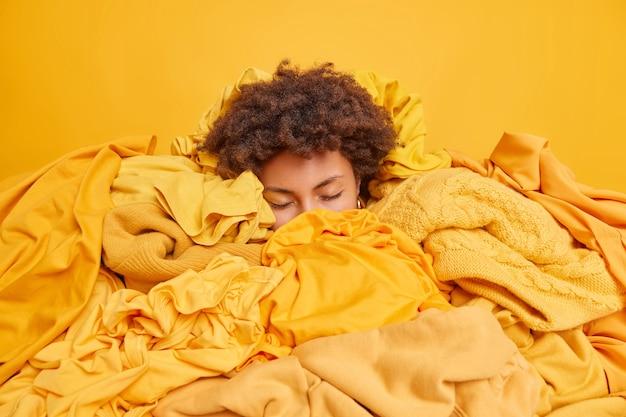 Mulher encaracolada cansada se sente exausta depois de fazer a limpeza do guarda-roupa na primavera, classifica as roupas por cor e cobertas com uma pilha de roupas mantém os olhos fechados, ocupada organizando o armário remove itens indesejados