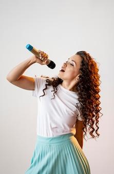 Mulher encaracolada cantando em um microfone dentro de casa