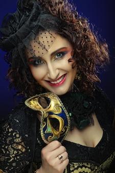 Mulher encaracolada com máscara. rosto de carnaval.