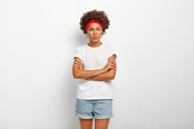 Mulher encaracolada com raiva e insultada franze a testa, fica de pé com as mãos cruzadas no peito e faz pose defensiva