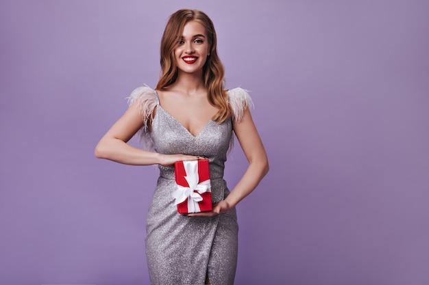 Mulher encaracolada com um lindo vestido prateado segurando uma caixa de presente vermelha