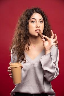 Mulher encaracolada comendo chocolate.