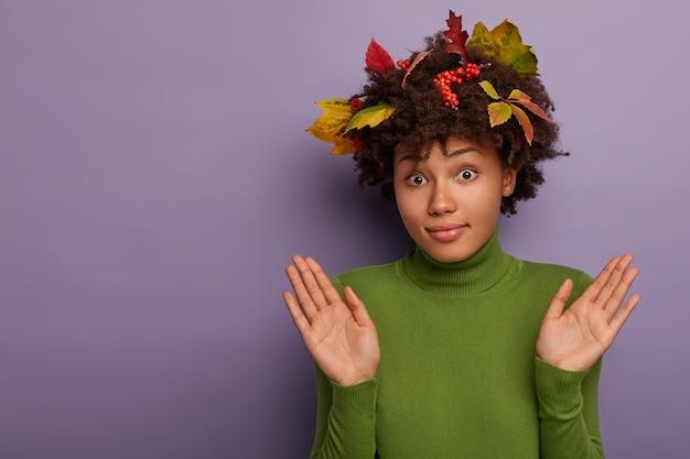 Mulher encaracolada confusa levanta as palmas das mãos, gesticula em estúdio, tem uma expressão facial sem noção, diz que não sou culpado, usa folhas coloridas de outono caídas e bagas de sorveira no penteado