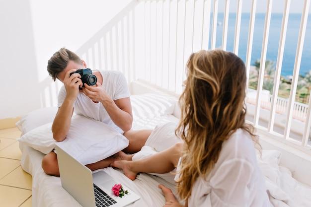 Mulher encaracolada de cabelos compridos em camisa branca, descansando na varanda com o computador, enquanto o marido dela tirando fotos. homem com câmera profissional tirando fotos de sua linda esposa pela manhã