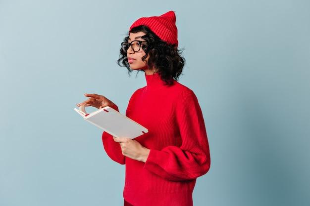 Mulher encaracolada de óculos segurando um caderno