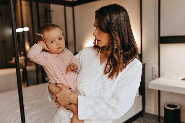 Mulher encaracolada de roupão de banho parece perplexa com a filha, colocando o telefone no ouvido. retrato de mãe e bebê no quarto luminoso.