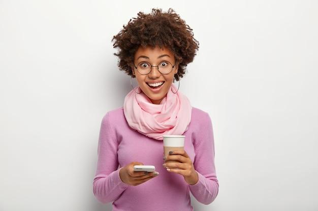 Mulher encaracolada divertida e simpática usa celular e bebe café para viagem, está de bom humor, surfa nas redes sociais